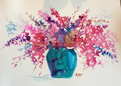 Blue glass vase of cherry blossom .