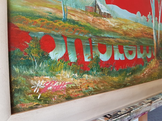Red coloured fashion brand stencilled onto a landscape painting of the Australian outback.