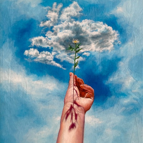 A hand holding a flower with bright blue sky and clouds in the background