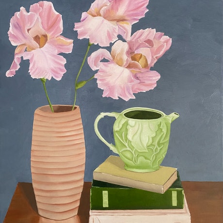 Pink irises in vase with teapot and books