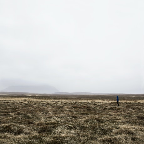 A wintery grey sky above a field of grey grass. A figure in blue looks out across the landscape.