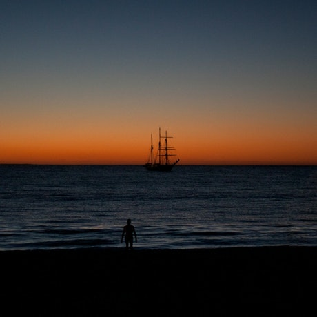 A deep orange sunset over navy water. A silhouette figure walks towards the inky sea. A tall ship is in the horizon.
