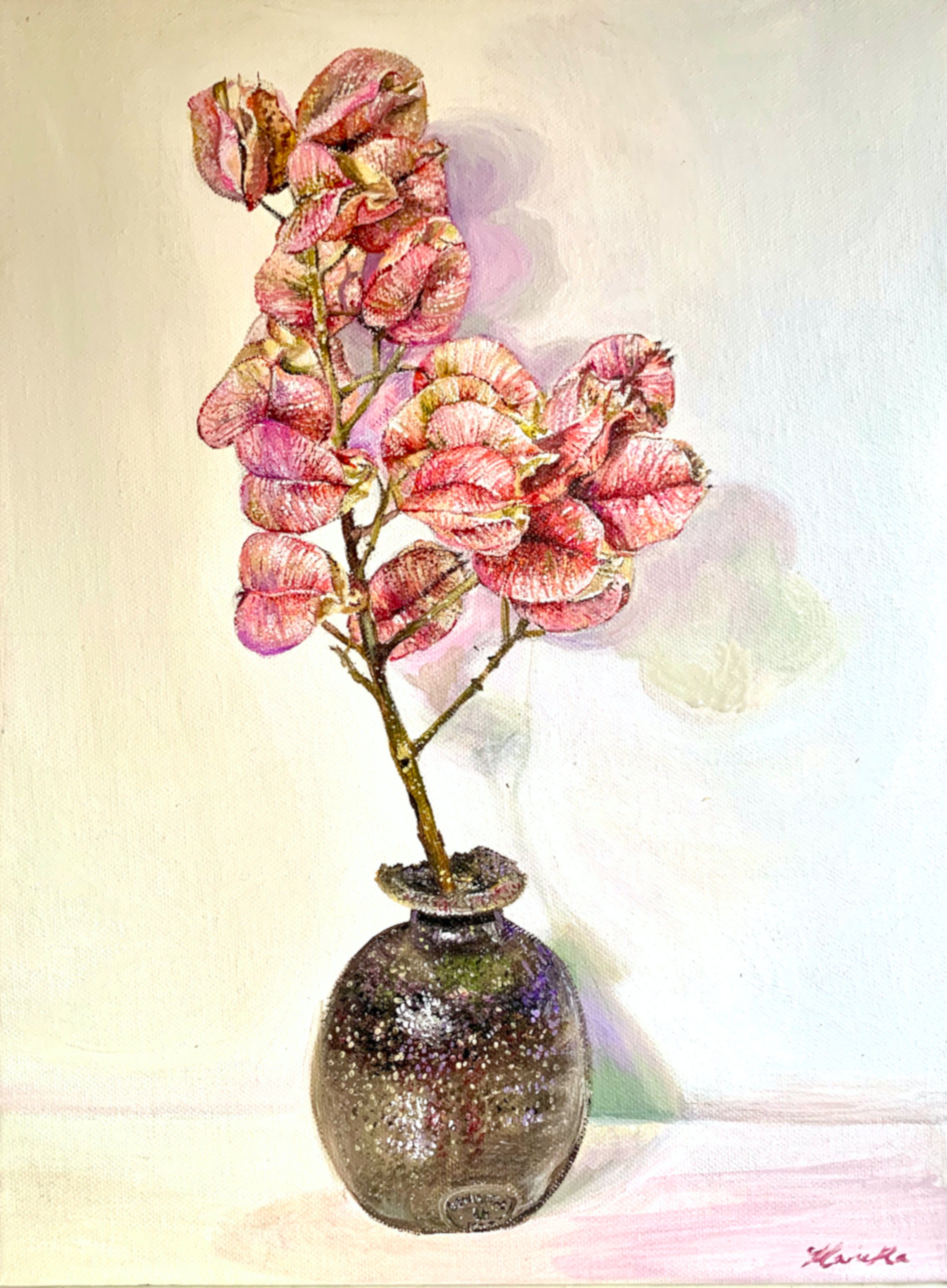 Pink seed pods from the Yellow Rain tree in a brown chipped vase sitting on a table.