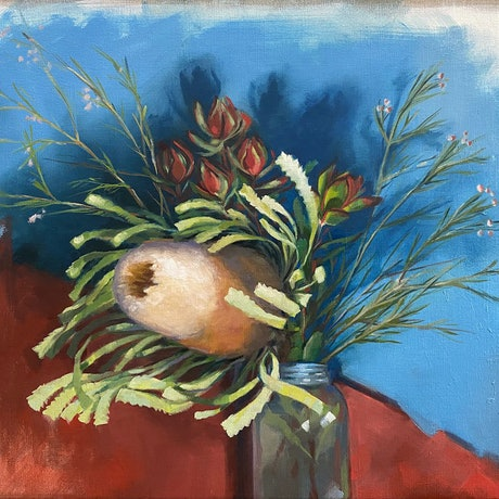 Oil painting of Australian banksia flower in a glass bottle with bold red and blue background.