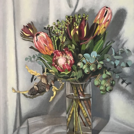 Native flowers in glass vase on white cloth
