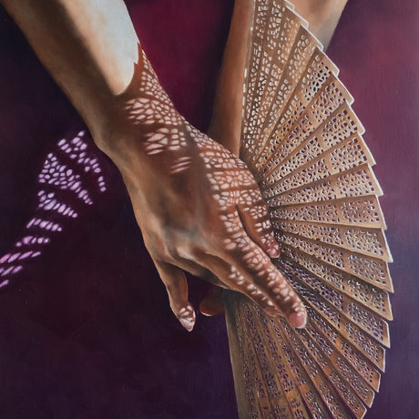 Two hands holding a lace patterned fan