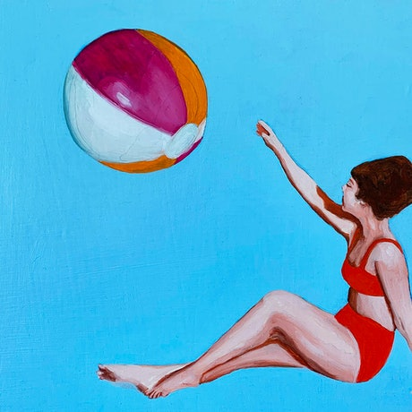 A woman sitting in a blue background reaching for a beach ball