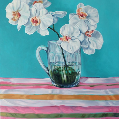 White orchids in glass stein sitting on stripes
