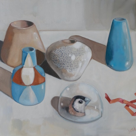 An arrangement of small contemporary vases and vessels in neutral tones part from a deep grecian blue. There is a small glass dome in the bottom right that has the head of a double barred finch in it gazing up at the arrangement. A small starched orange ribbon leads your eye off of the canvas on the right.