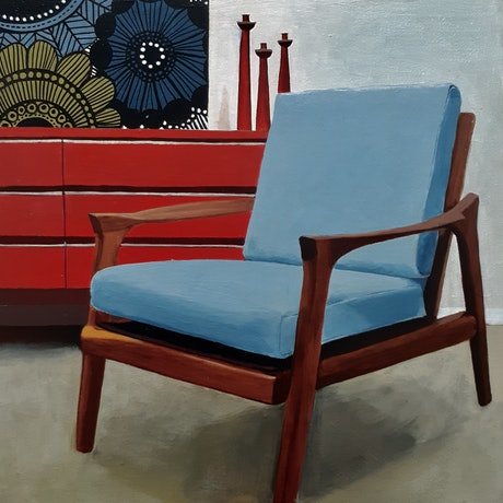 Mid century blue Parker chair in room with mid century sideboard that has a boldly patterned artwork resting on it.
