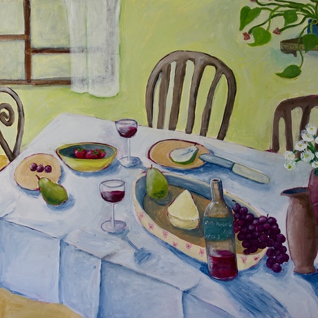 A table setting in a green room. On the table there is wine, fruit and flowers. There are empty chairs around the table. There is a window behind the table which lets light into the room and creates shadows.