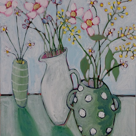 An assortment of impressionistic, delicate flowers in three different vessels. Muted, calming colours.