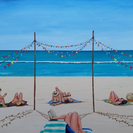 People lying on beach under colourful bunting