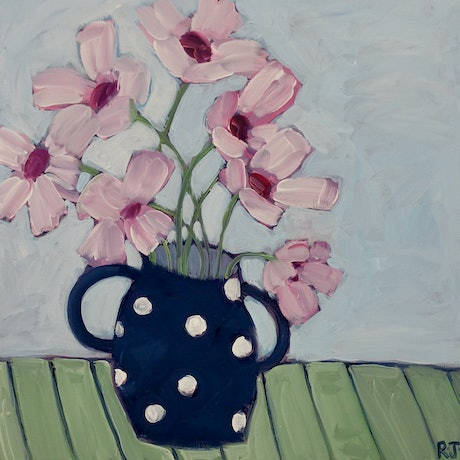 Large semi-abstract pink flowers in a navy pot with white spots. The background is light blue. The navy pot sits on a green surface,