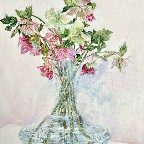 Bunch of pink and green Hellebores in a glass vase on a table with colourful shadows and reflections.