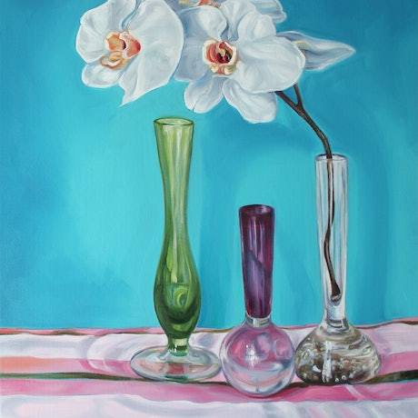 White Orchid flowers in 1950s glass bubble vases on a vintage striped sheet.