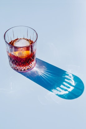 A Negroni cocktail in sunlight casting a shadow against a blue background.