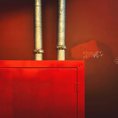 Urban industrial landscape with a textural red  wall and steel pipes