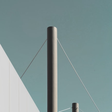 A surreal and minimalist image of poles connected by wire set against an aqua sky