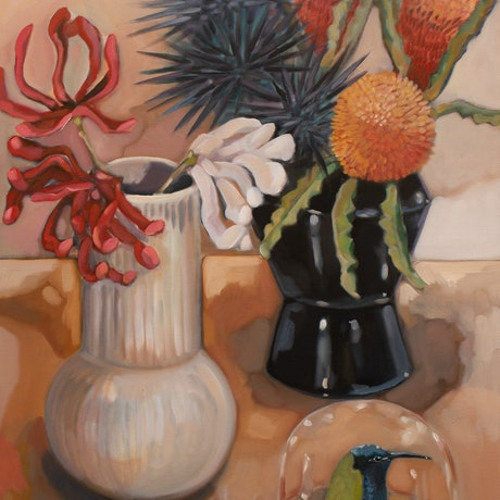 Two contemporary shapes vases , the vase in the background is angular and black in colour, the vase in he front is white and a more bulbous in shape with a narrow neck. The vases holed orange banksia stems, stacked purple urchins and some red  and white flowers that may or may not be real. There is a glass dome in the bottom right holding a taxi dermy style bird head.