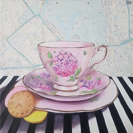 Pink floral tea cup with biscuits and map