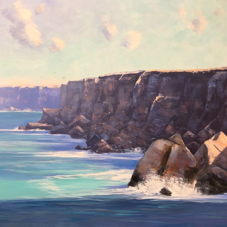 Huge cliffs and boulders with a turquoise sea.
