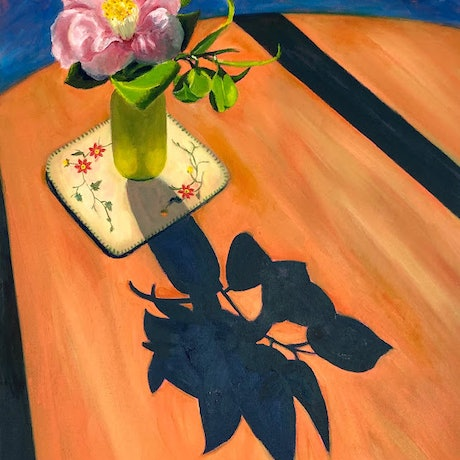 Pink camellia flower in a yellow vase on a table.  Long shadows.  Blue background.
