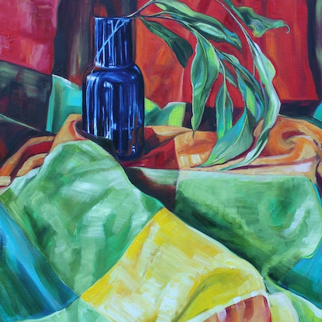 A vintage blanket wraps in bright colours around a blue glass vase holding a Eucalyptus branch