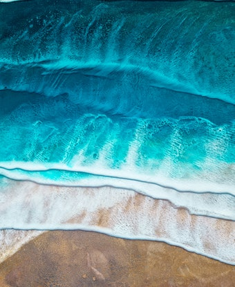 Turquoise ocean and crashing white waves onto a golden shore
