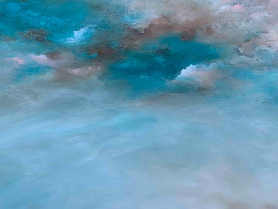 Blue and teal sunny cloudscape overlooking brown rocky mountains with green trees
