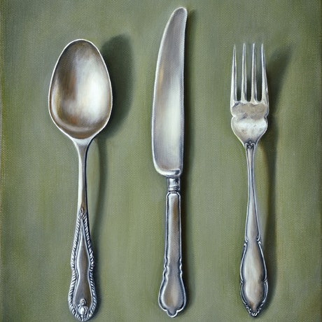 Vintage silver cutlery on olive colour background.