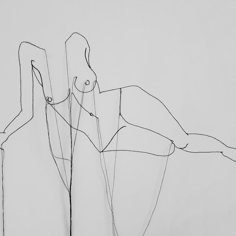 Nude figure lying on side stitched drawing with hanging thread on paper.