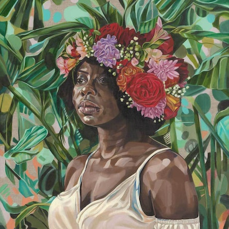 Beautiful, strong black woman, wearing a crown of flowers in front of a leafy green backdrop.