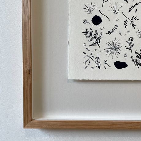 A large white piece of watercolour paper has many dark pigment images of abstracted forms from the landscape. Shapes of stones, native plants, branches, line patterns, ferns, wattle and various other abstracted lines fill the paper.