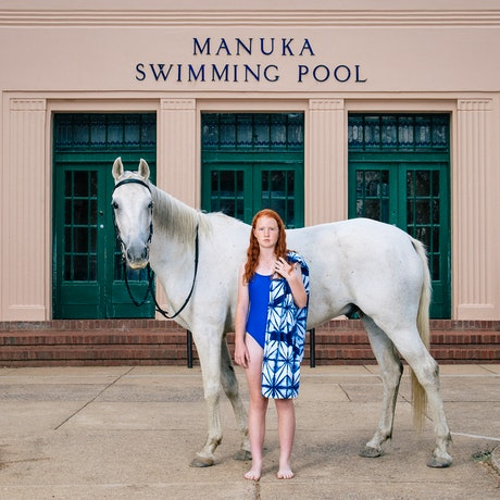 young girl with her horse standing in front of a building