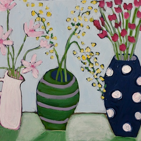 three pots containing flowers with a light blue background