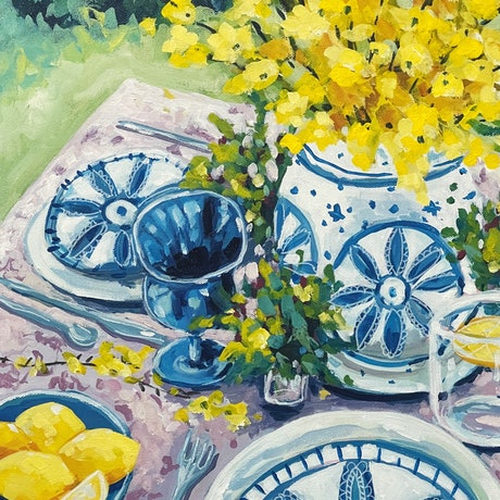 Table set with plates and a vase of yellow flowers