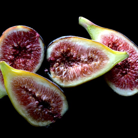 Four pieces of fig on a black background